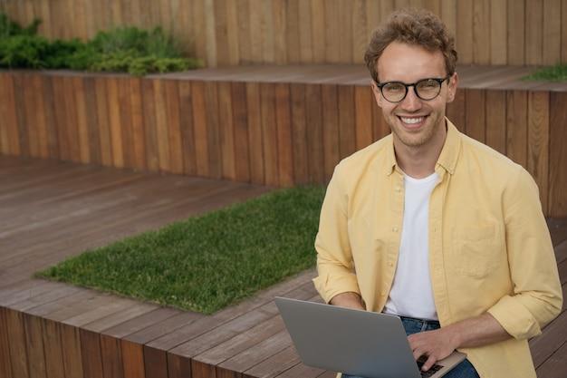 Un bell'uomo d'affari sorridente che indossa occhiali utilizzando la pianificazione del laptop inizia a lavorare da casa
