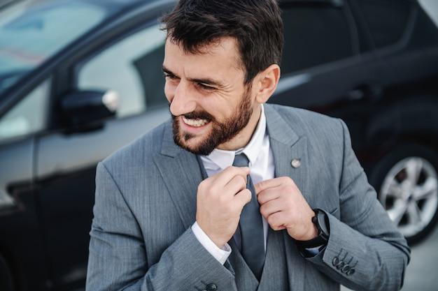 Uomo d'affari barbuto caucasico sorridente bello in vestito che fissa la sua cravatta. sullo sfondo c'è la sua macchina.