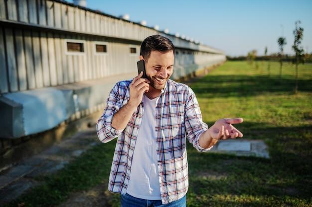 Coltivatore caucasico sorridente bello in camicia a quadri e jeans in piedi all'aperto e parlando al telefono