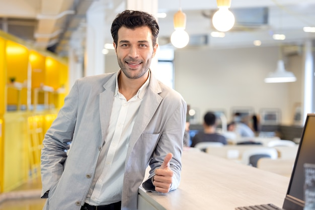 Ritratto di uomo d'affari fiducioso sorridente bello, resta affamato di successo all'interno di un ufficio ad alta tecnologia