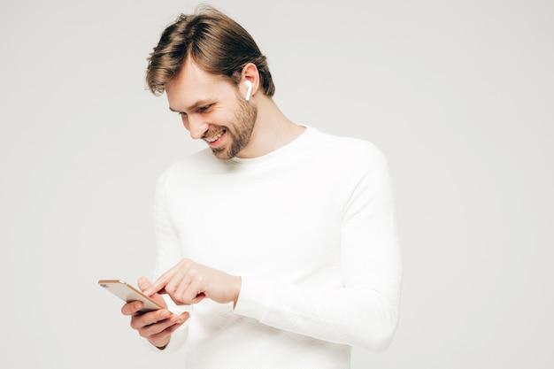Bello sorridente modello di uomo d'affari lumbersexual hipster che indossa pantaloni e maglione casual bianco. moda uomo alla moda in posa contro il grigio
