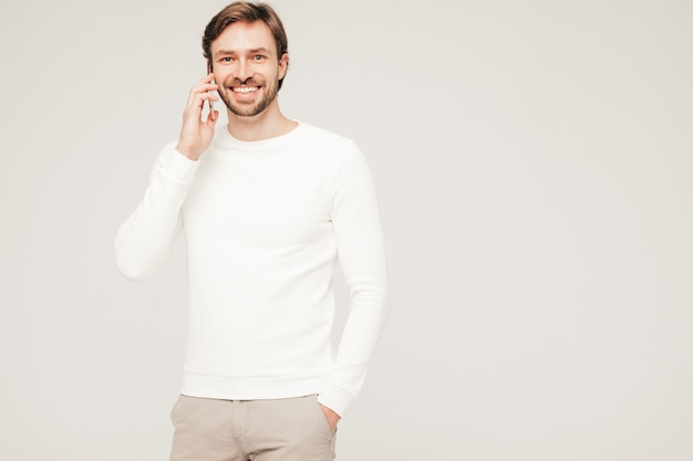 Bello sorridente hipster lumbersexual modello di uomo d'affari che indossa un maglione bianco casual e pantaloni