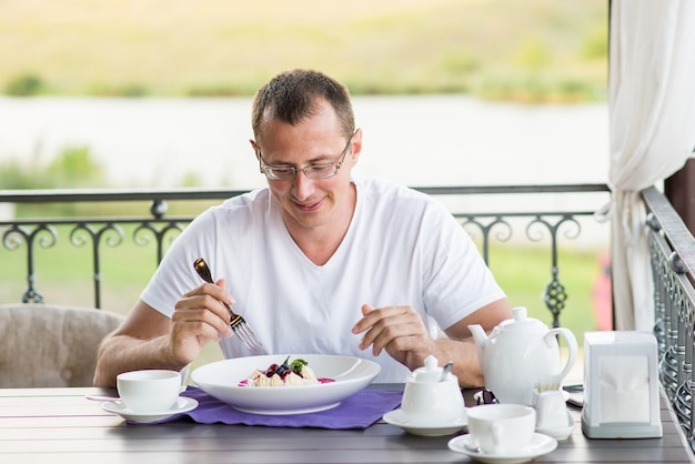 Uomo sorridente bello che mangia dessert in un ristorante all'aperto