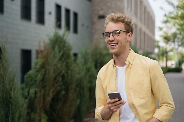 Bell'uomo sorridente che usa il cellulare in attesa di un taxi all'aperto