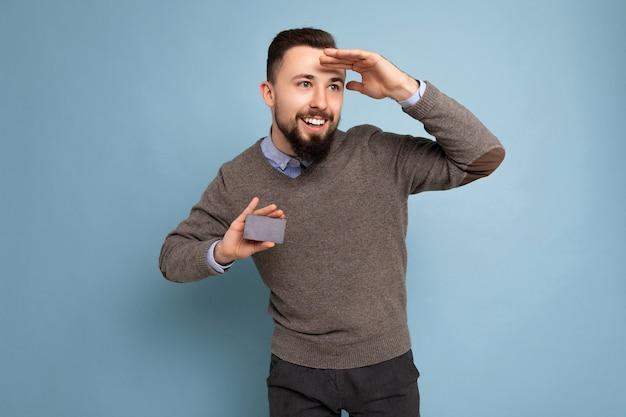 Uomo sorridente bello che indossa un maglione grigio e camicia blu che tiene la carta di credito che osserva al lato