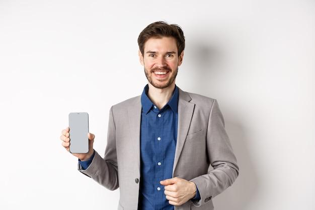 Venditore sorridente bello in vestito che mostra lo schermo vuoto dello smartphone, dimostrare un'app, in piedi su sfondo bianco.