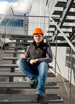 Bello lavoratore sorridente che si rilassa sulla scala di metallo durante la pausa