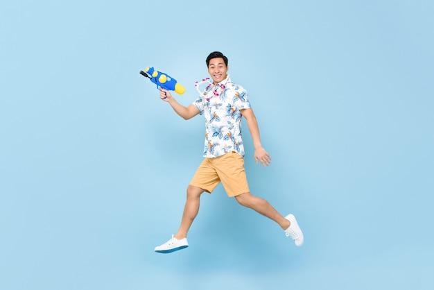 Giovane uomo asiatico sorridente bello che gioca con la pistola ad acqua e che salta per il festival di songkran in tailandia e sud-est asiatico