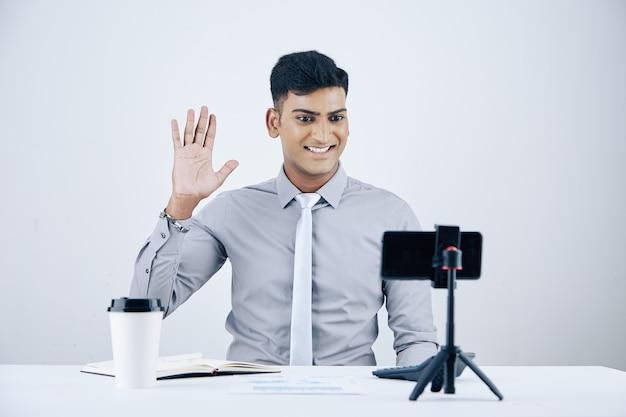 Bel giovane imprenditore indiano sorridente seduto alla scrivania con una tazza di caffè da asporto e videochiamando il suo collega o socio in affari