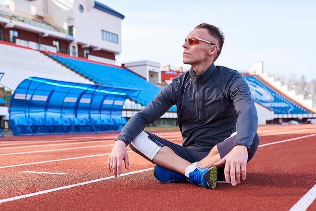 Un bell'uomo sportivo siede in una posa di loto sul tapis roulant dello stadio