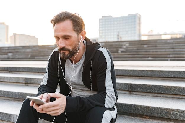 Bello sportivo in auricolari tenendo il telefono cellulare