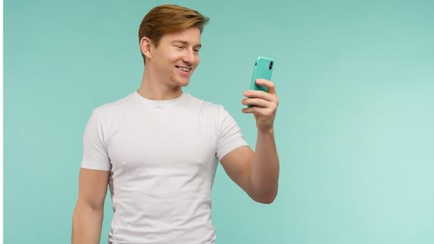 Bel ragazzo dai capelli rossi sportivo in maglietta bianca prende un selfie o trasmette online su uno smartphone su sfondo blu. - immagine