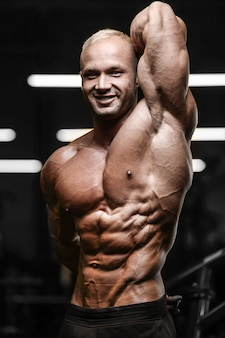Uomo atletico forte bello che pompa i muscoli allenamento fitness e concetto di bodybuilding - bodybuilder muscolare uomini fitness facendo esercizi addominali braccia in palestra torso nudo