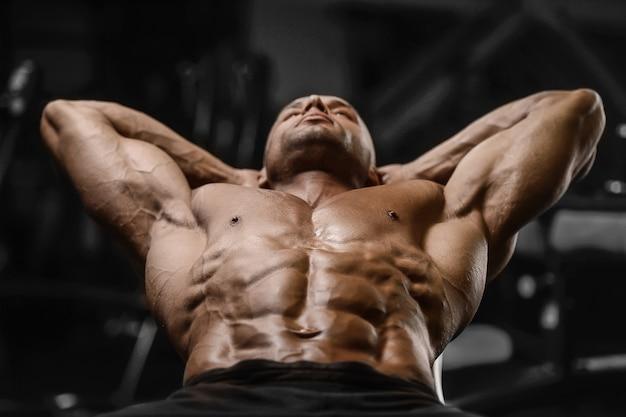 Uomini atletici forti bei che pompano su concetto di forma fisica e di culturismo di allenamento dei muscoli - l'uomo muscolare di forma fisica del culturista che fa gli addominali si esercita nel torso nudo della palestra