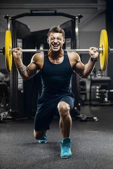 Uomini atletici forti belli che pompano sul concetto di fitness e bodybuilding di allenamento dei muscoli
