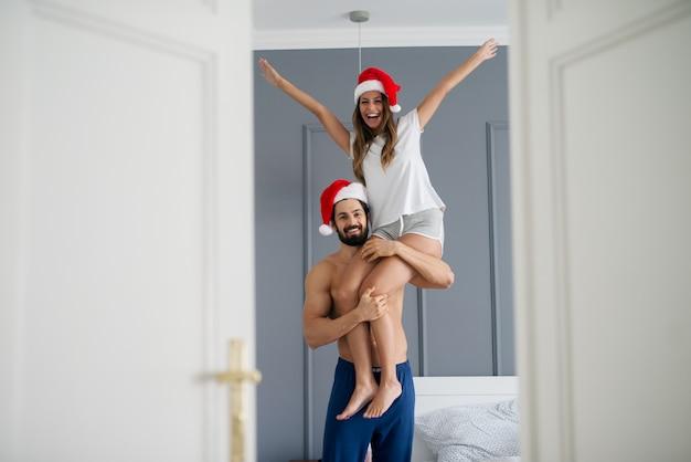 Uomo senza camicia forte bello con il cappello di natale che tiene la sua ragazza su una spalla nella camera da letto.