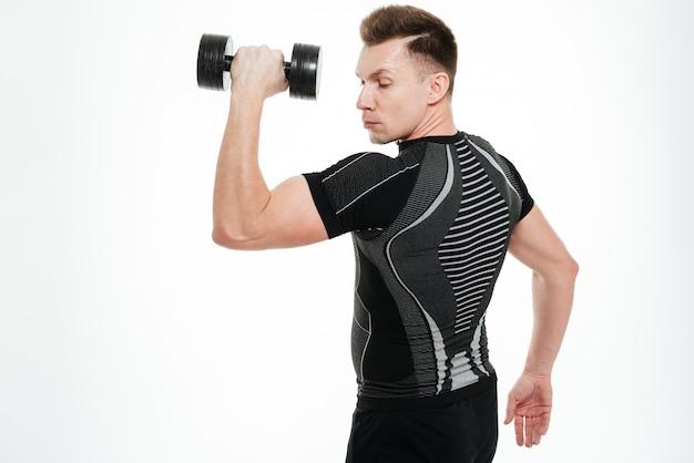 Lo sportivo forte bello fa gli esercizi di sport con la testa di legno