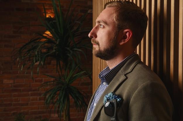 Bell'uomo di stoppie in moderna giacca verde in piedi vicino al muro di legno in appartamento loft