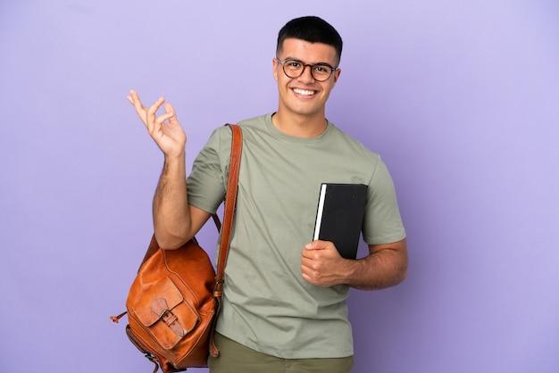 Bell'uomo studente su sfondo isolato che estende le mani ai lati per invitare a venire