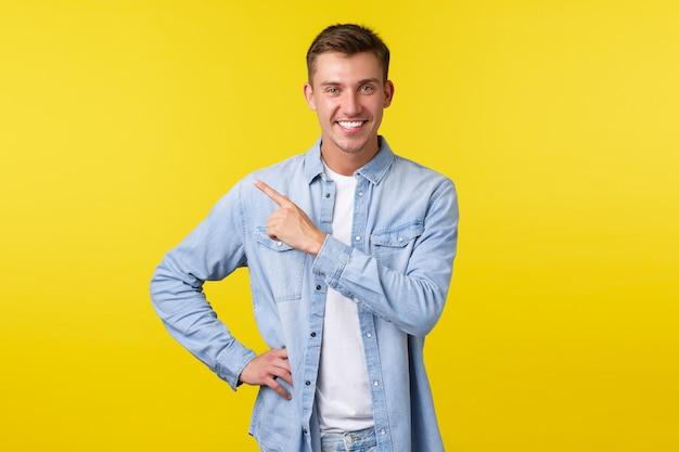 Bello ed elegante uomo adulto biondo con un sorriso bianco che punta il dito nell'angolo in alto a sinistra sul dorso giallo...