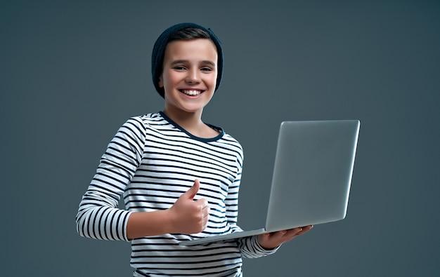 Il ragazzo alla moda bello in un maglione a righe e un cappello con un computer portatile in mano mostra un pollice in alto isolato su un grigio.