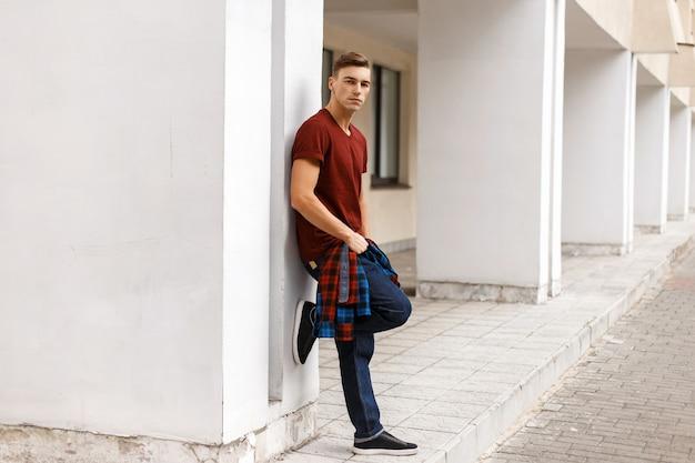 Uomo alla moda bello che tiene una camicia e pose vicino al muro bianco.