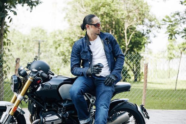 Bell'uomo elegante seduto in moto con una tazza di caffè da asporto e guardando lontano