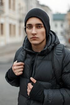 Bel giovane alla moda con un cappello nero e una giacca invernale