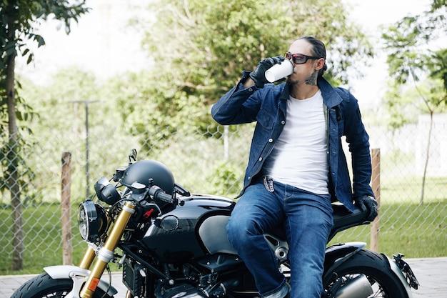 Bel giovane elegante che beve una tazza di caffè da asporto dopo un lungo giro in moto