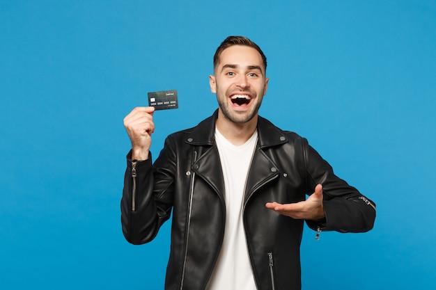 Bel giovane uomo con la barba lunga alla moda in giacca di pelle nera t-shirt bianca tenere in mano carta di credito isolata su parete blu sfondo ritratto in studio. concetto di stile di vita della gente. mock up copia spazio.