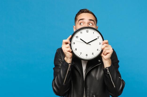Bello elegante giovane uomo con la barba lunga in giacca di pelle nera t-shirt bianca che tiene orologio rotondo isolato su parete blu sfondo ritratto in studio. concetto di stile di vita della gente. sbrigati. mock up copia spazio.