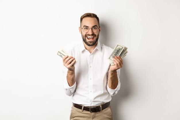 Un bell'uomo d'affari di successo che conta soldi, si rallegra e sorride, in piedi su sfondo bianco