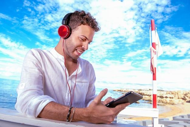 Uomo caucasico bello e di successo che ascolta musica audio sulla spiaggia. freelance e lavoro a distanza. studente sulla sponda mediterranea