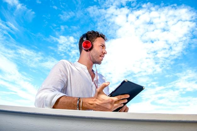 Uomo caucasico bello e di successo ascoltando musica sulla spiaggia. freelance e lavoro a distanza. studente sulla sponda mediterranea