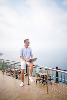 Il giovane uomo d'affari maschio riuscito bello che lavora con il computer portatile esamina il mar mediterraneo. indossa una maglietta e pantaloncini bianchi. lavoro a distanza in vacanza. concetto di vacanza