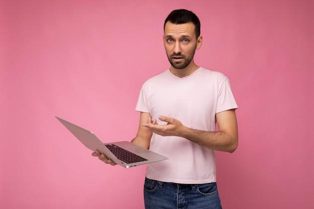 Bello sorpreso e stupito uomo brunet tenendo il computer portatile che mostra al netbook guardando la fotocamera in t-shirt su sfondo rosa isolato.