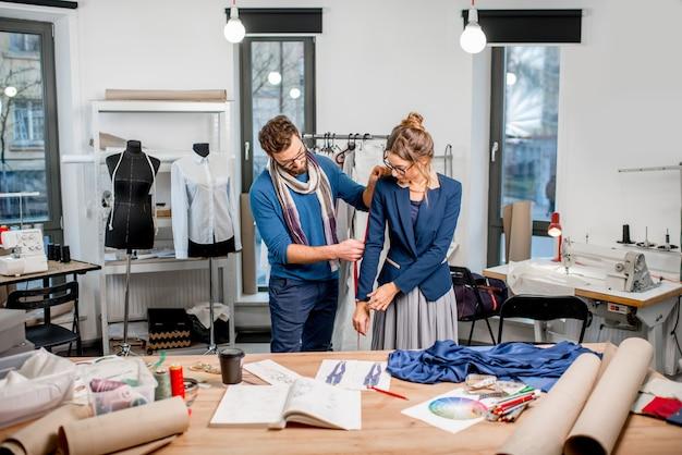 Bella giacca di misurazione del sarto sul cliente donna in piedi nello studio pieno di strumenti e attrezzature sartoriali Foto Premium