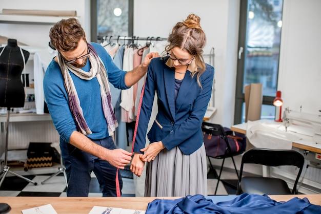 Bella giacca di misurazione del sarto sul cliente donna in piedi nello studio pieno di strumenti e attrezzature sartoriali