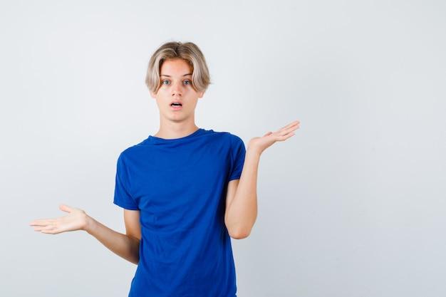 Bel ragazzo adolescente in maglietta blu che mostra gesto impotente e sembra sconcertato, vista frontale.