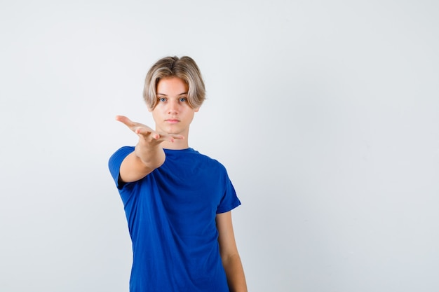 Bel ragazzo adolescente in maglietta blu che allunga la mano sul davanti e sembra fiducioso, vista frontale.