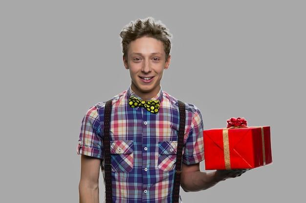 Contenitore di regalo teenager bello della tenuta del ragazzo. ragazzo adolescente con confezione regalo su sfondo grigio. celebrazione delle vacanze.
