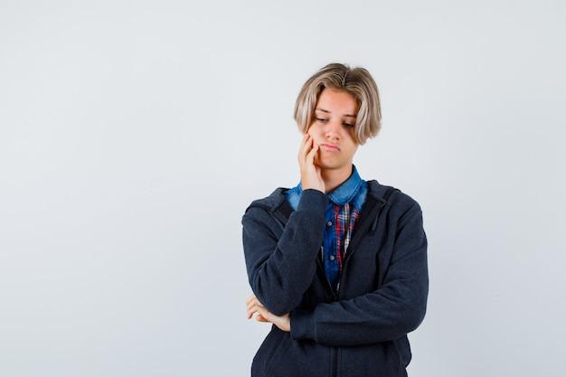 Bel ragazzo adolescente appoggiato sulla guancia a portata di mano, guardando in basso in camicia, felpa con cappuccio e guardando cupo, vista frontale.