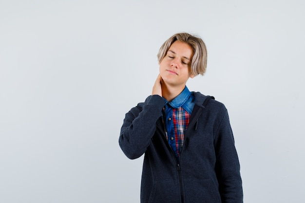Bel ragazzo adolescente in camicia, felpa con cappuccio che sente dolore al collo e sembra stanco, vista frontale.