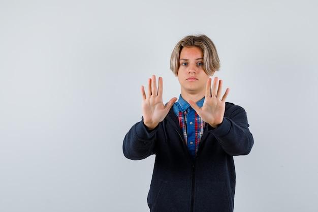Bel ragazzo adolescente in camicia, felpa con cappuccio che mostra il segnale di stop e sembra spaventato, vista frontale.