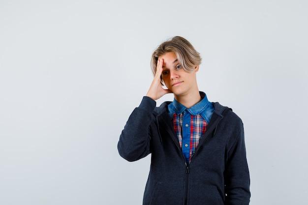 Bel ragazzo adolescente in camicia, felpa con cappuccio che soffre di forte mal di testa e sembra angosciato, vista frontale.