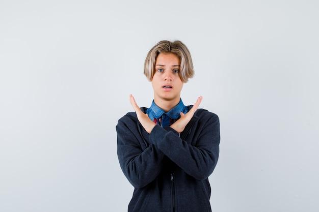 Bel ragazzo adolescente che mostra gesto di rifiuto in camicia, felpa con cappuccio e sembra agitato, vista frontale.