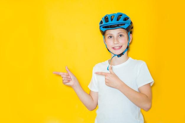 Bel ragazzo adolescente che indossa il casco di sicurezza del ciclista su sfondo giallo isolato. concetto di vincitore