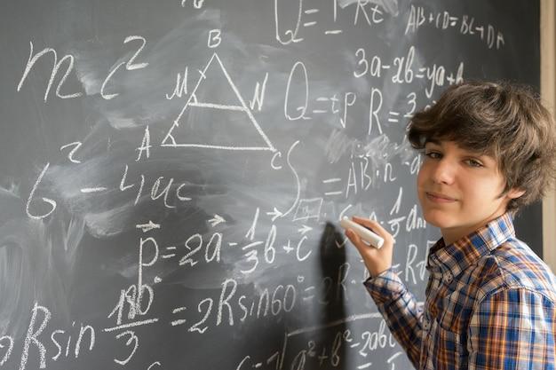 Bel ragazzo adolescente con gesso scrivendo complicate formule matematiche sul bordo nero