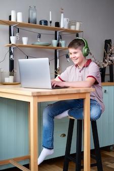 Bel ragazzo adolescente in cuffia studiando online, giocando ai videogiochi utilizzando laptop seduto sulla cucina.