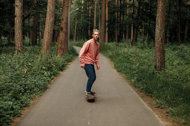 Bell'uomo adolescente in un maglione rosa e blue jeans cavalca su uno sketchboard nel parco